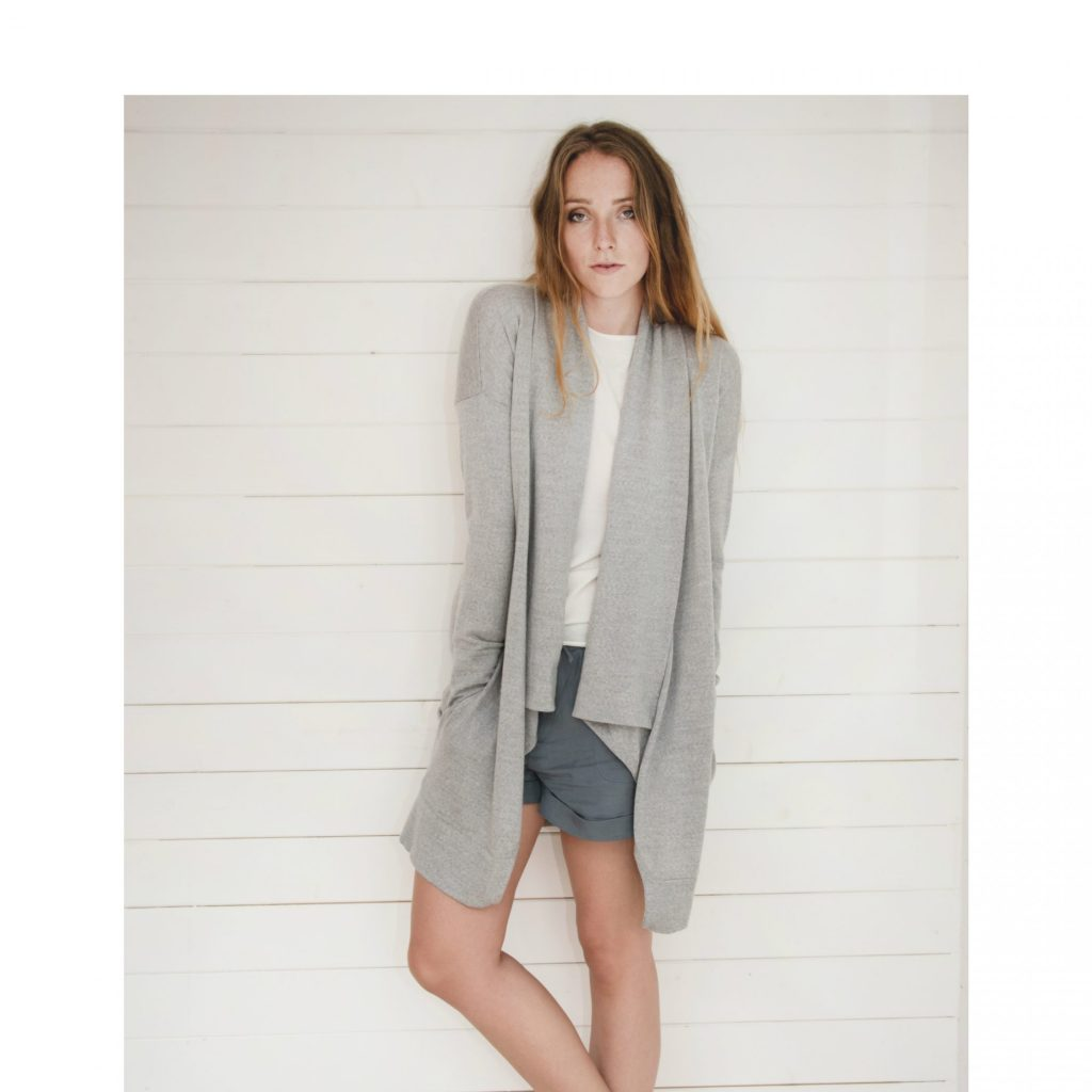 Model wears Kate Cardigan knitted in extra fine grey merino wool.